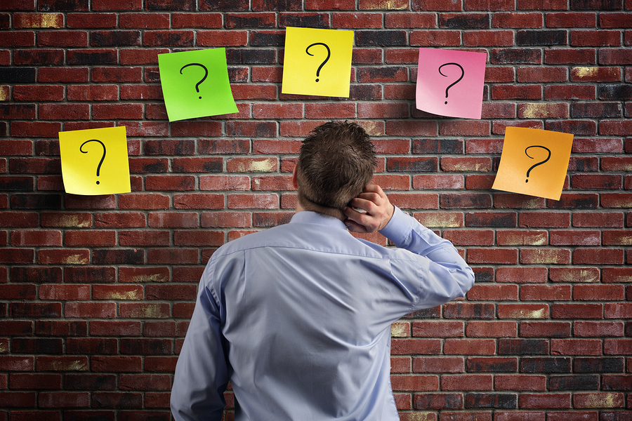 Choice and decisions: businessman thinking with question marks written on adhesive notes stuck to a brick wall